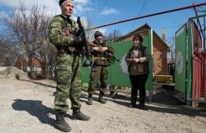 Soldiers of the Donetsk People's Republic speak to a resident in the frontline town of Shirokino, some 10 kms east of Mariupol, on March 20, 2015 (AFP Photo/John MacDougall)