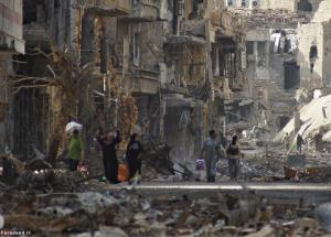Residents and a Free Syrian Army fighter walk along a street lined with damaged buildings in Deir al-Zor