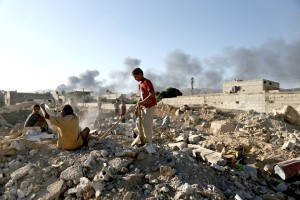 Children inspect rubble fromclashes between al-Assad's force and Army of Islam (--Bassam Khabieh/Reuters)